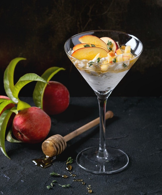 Ricotta dessert with sliced peach, thyme and honey, served in cocktail glass with whole peaches, leaves and honey-dipper over dark textured background. Summer sweets theme.
