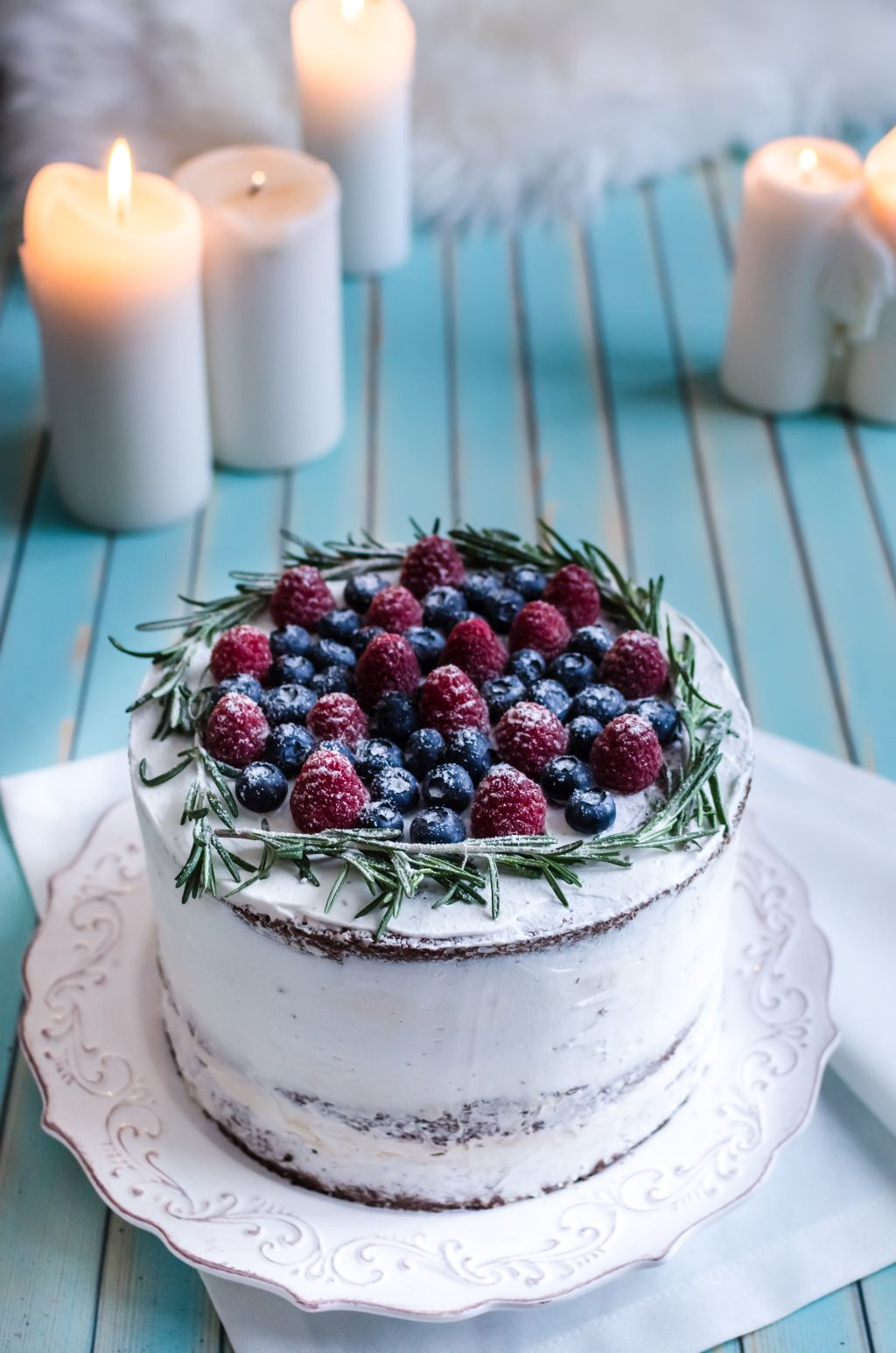 Homemade chocolate nutty naked birthday cake with white cream on each side, decorated with raspberries, blueberries, rosemary on serving plate with white napkin over wooden turquoise table, candles on the background, selective focus